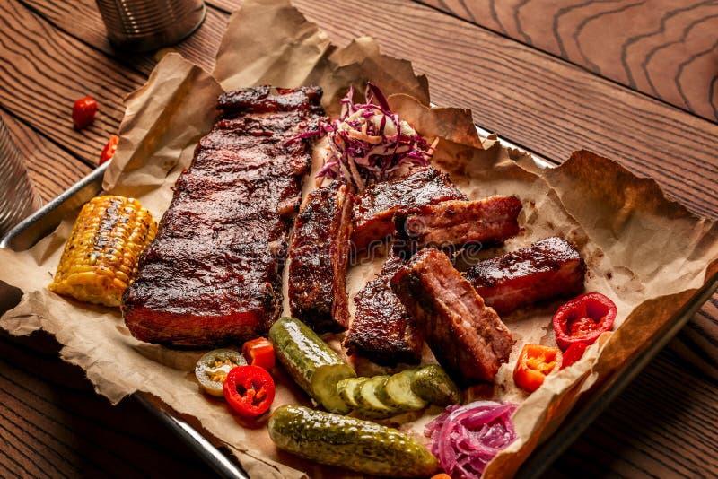 Les nervures de porc grillées ont servi avec du maïs, le salat, la sauce à BBQ, le poivre de sel et le concombre grillés sur le p images stock