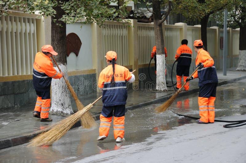 Les nettoyeurs balayent la rue photos libres de droits