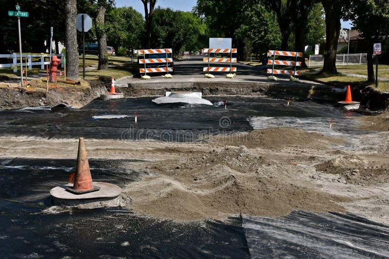 Les niveleuses de route nivelle le sable dans un projet de construction de routes images stock