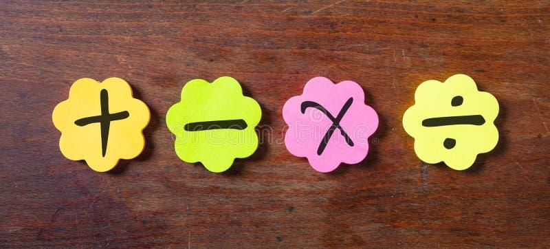 Les notes colorées collantes en fleur forment, avec des symboles de maths sur le fond en bois photographie stock libre de droits