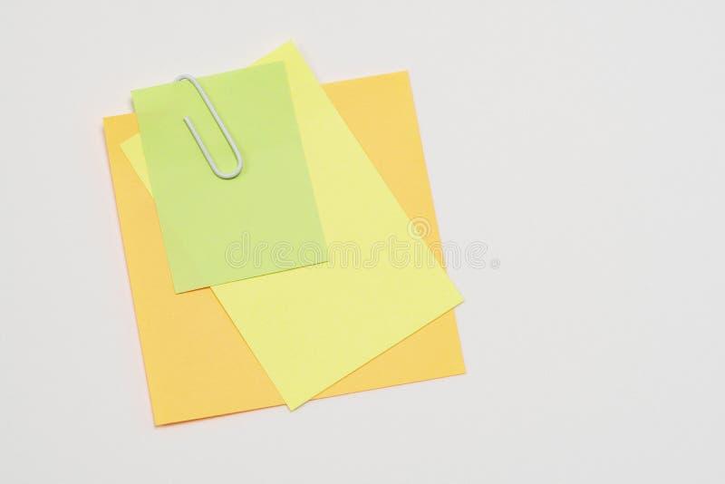 Les notes de papier multicolores ont attaché avec un trombone sur un fond blanc photos stock