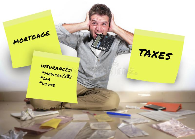 Les notes de post-it mensuelles de dépenses et l'homme d'affaires criant la dette calculatrice désespérée et accablée ont soumis  photographie stock