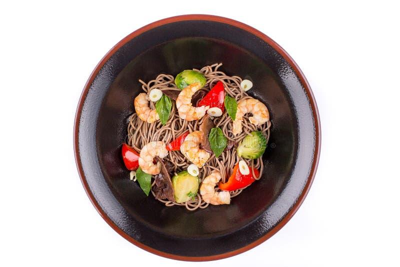 Les nouilles de sarrasin avec des crevettes et le teriyaki sauce, d'isolement sur le fond blanc Nouilles de sarrasin dans un plat photo stock