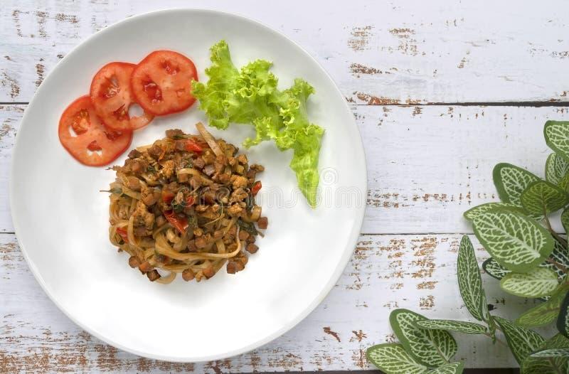 Les nouilles frites avec du porc, le basilic, l'ail et les piments coupés ont mis dessus c photo stock