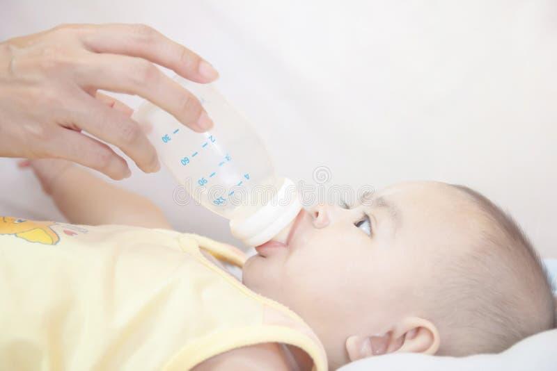 Les nourrissons âgés 5-6 mois sont lait boisson de la bouteille Par les mains de la mère image stock