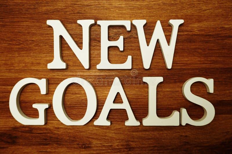 Les nouveaux buts expriment des lettres d'alphabet sur le fond en bois photographie stock libre de droits