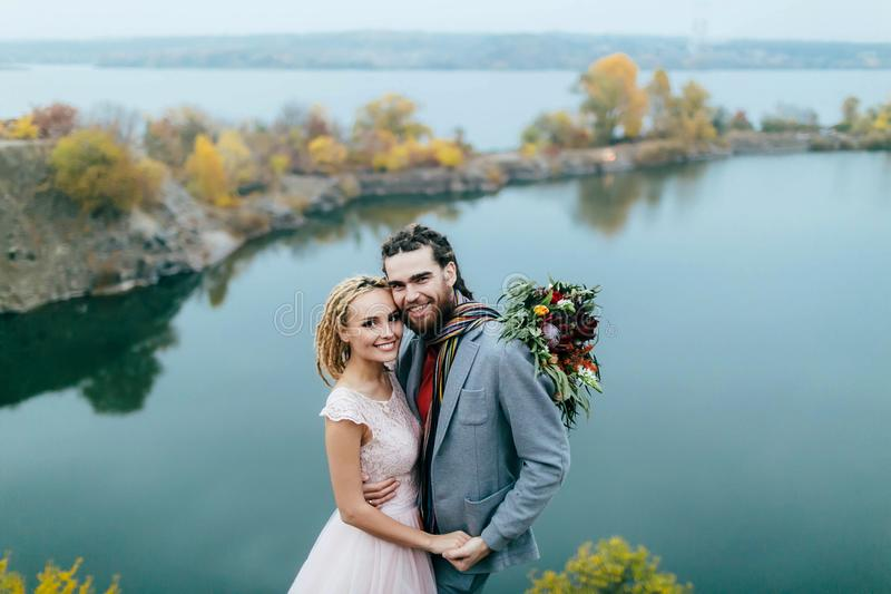 Les nouveaux mariés élégants de couples posent avant un lac sur la colline Cérémonie de mariage d'automne dehors Plan rapproché photo stock