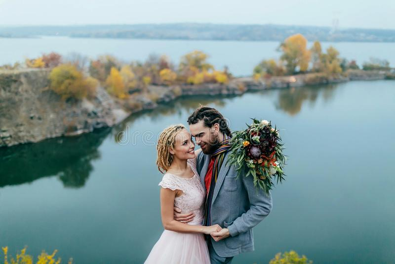 Les nouveaux mariés élégants de couples sourient et étreignant la position avant un lac Jeunes mariés avec le regard de dreadlock photographie stock