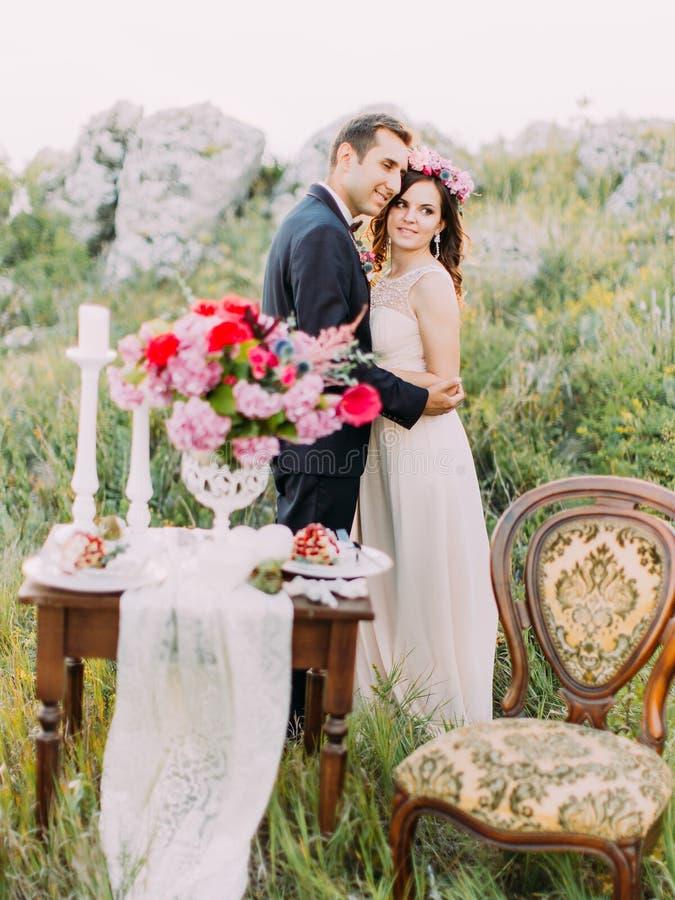 Les nouveaux mariés étreignants derrière la composition brouillée de la table de mariage ont placé dans les montagnes photos stock