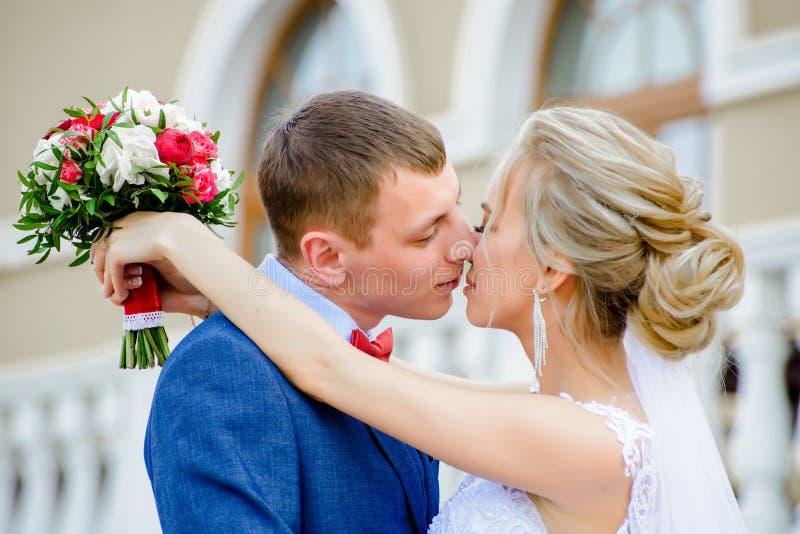 Les nouveaux mariés embrassent à la profondeur du champ photos libres de droits