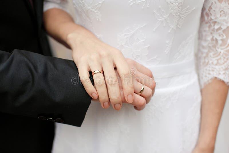 Les nouveaux mariés, les mains de prise de jeunes mariés avec des anneaux de mariage photo libre de droits