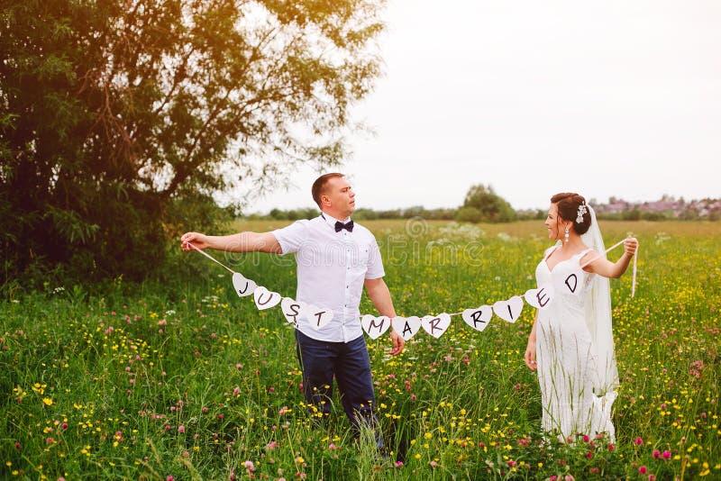 Les nouveaux mariés restent sur le pré avec juste le signe marié photo stock