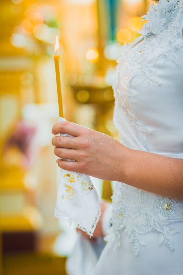 Les nouveaux mariés tiennent des bougies sur la cérémonie de mariage images libres de droits