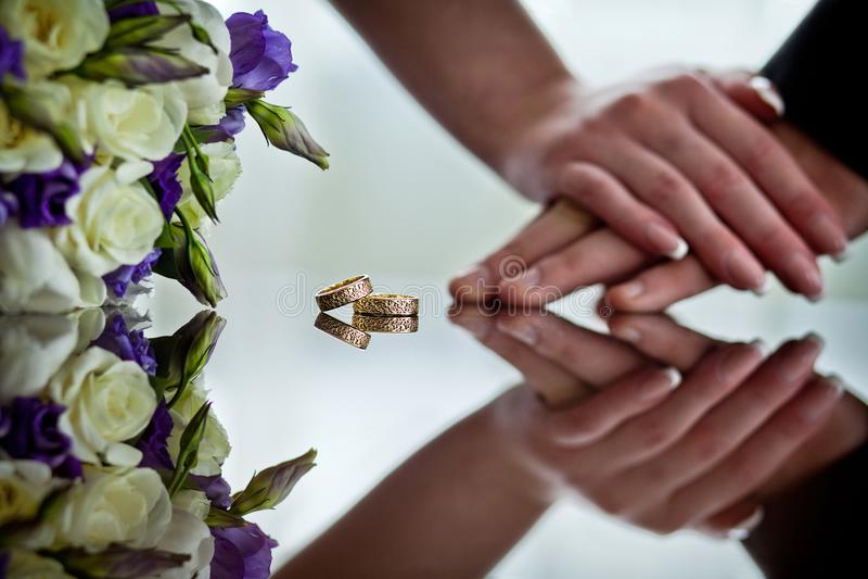 Les nouveaux mariés tiennent des mains à côté des anneaux de mariage qui se trouvent sur la surface de miroir photographie stock