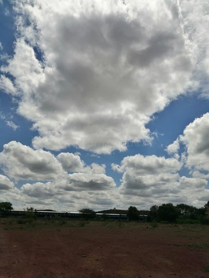 Les nuages blancs de neige comme ils planent au-dessus de la joie de propagation de la terre aux enfants images libres de droits