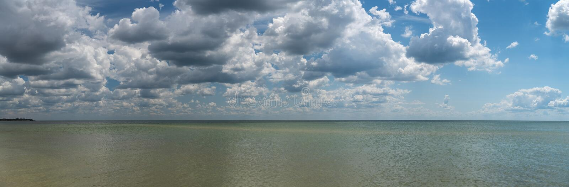 Les nuages blancs flottent dans le ciel au-dessus de la côte photos stock