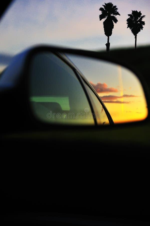 Les nuages de coucher du soleil ont reflété le miroir de véhicule images libres de droits