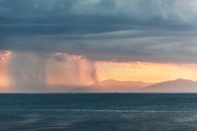 Les nuages de pluie en plaines éloignées s'approchent des montagnes photos stock