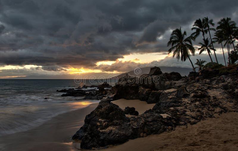 Les nuages de tempête au coucher du soleil sur Hawaï échouent images stock