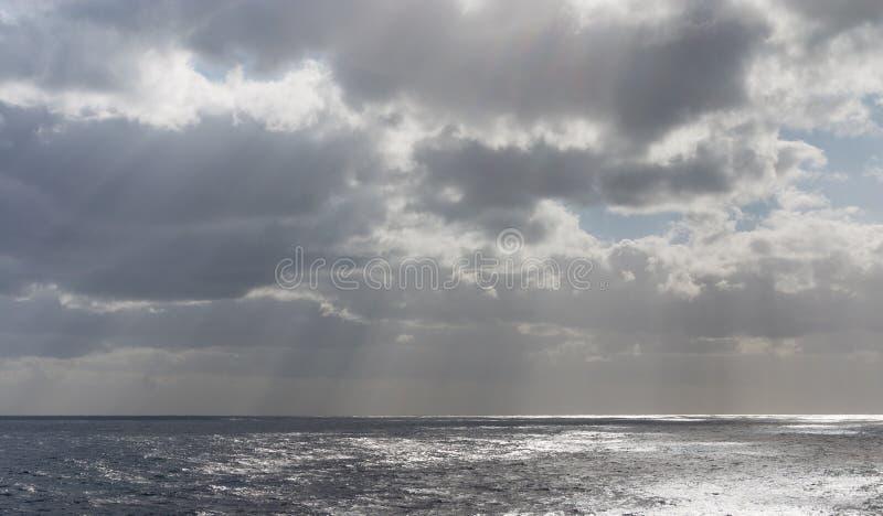 Les nuages de tempête avec le soleil rayonne sur l'océan image stock