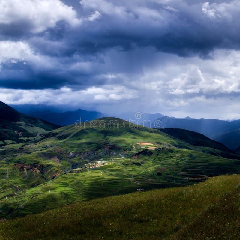 Les nuages de tempête roulent dans au-dessus d'un petit village de Sichuan photographie stock libre de droits