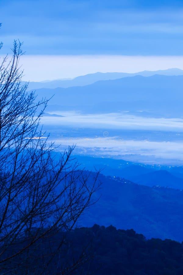 Les nuages et le ciel bleus fantastiques de lever de soleil sur la gamme bleue de montagne, brouillent des points de lampe au néo photo stock