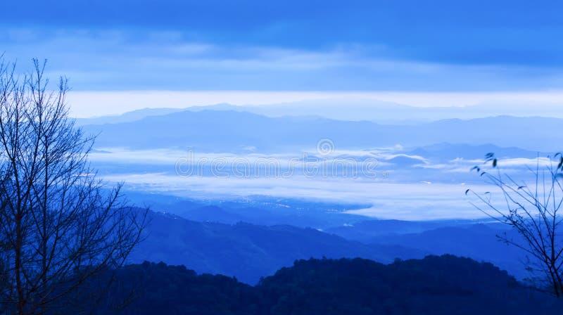 Les nuages et le ciel bleus fantastiques de lever de soleil sur la gamme bleue de montagne, brouillent des points de lampe au néo photographie stock