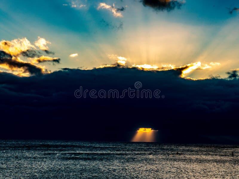 Les nuages foncés ont enveloppé le soleil, et le soleil s'est reflété de nouveau dans le ciel, passant par les nuages minces dans images stock