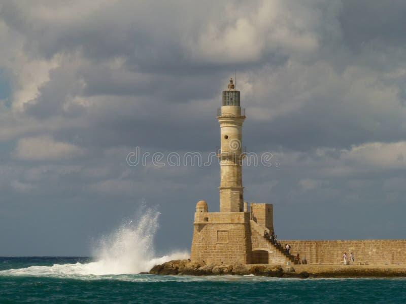 Les nuages gris sombres accrochent au-dessus du phare des briques jaunes et blanches dans Chania, au sujet duquel les vagues se b photo stock
