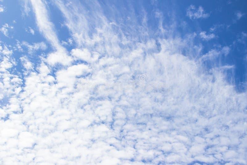 Les nuages pelucheux blancs dans le ciel bleu soustraient le fond photos stock