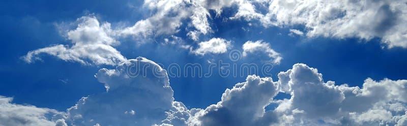 Les nuages réfléchissent la lumière dans le ciel bleu lumineux photo libre de droits