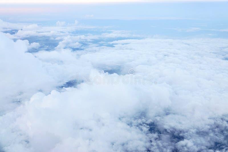 Les nuages regardent de la fenêtre d'avion au ciel bleu photos stock