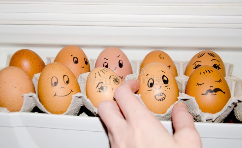 Les oeufs avec la cellule peinte d'oeufs d'émotions dans la main de réfrigérateur choisit l'oeuf Oeuf effrayé, psychologie de la  image libre de droits