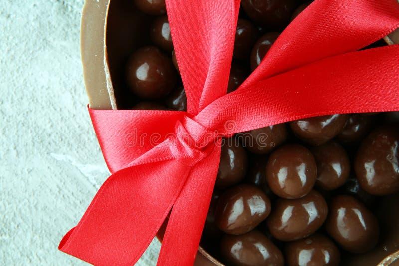Les oeufs de pâques de chocolat avec le ruban de couleur cintre sur le backgrou de vintage images libres de droits