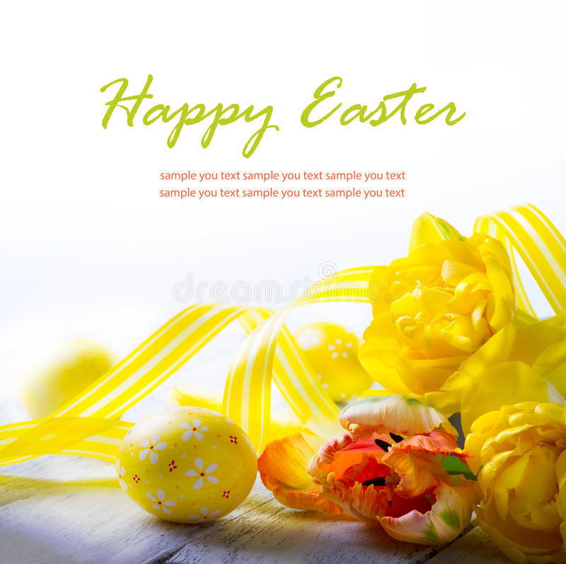 Les oeufs de pâques d'art et le ressort jaune fleurissent sur le fond blanc images stock