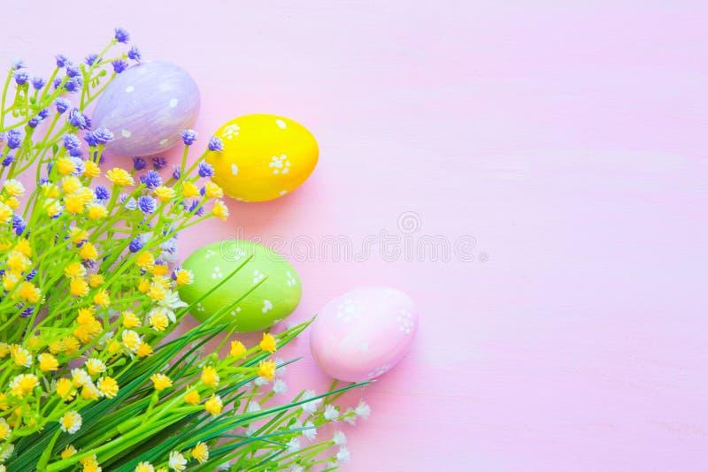 Les oeufs de pâques dans la couleur en pastel avec des fleurs sur en bois pâlissent - le fond rose Vue supérieure photographie stock