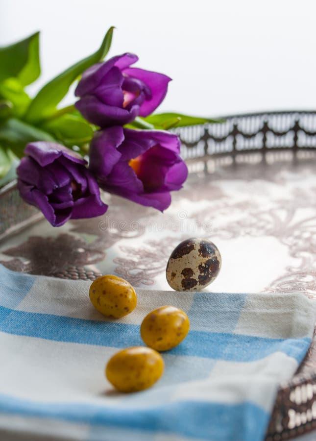 Les oeufs de pâques et les tulipes violettes sur le vintage argentent le plateau images stock