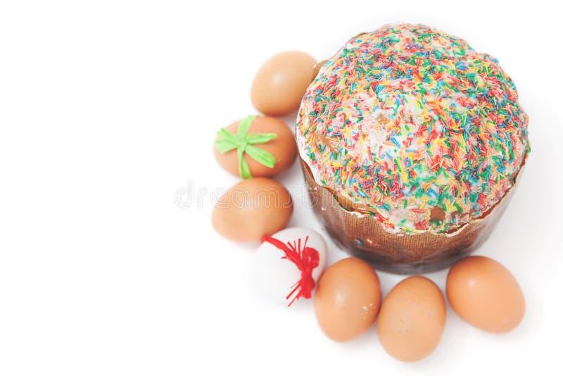 Les oeufs de pâques se trouvent autour du gâteau sur le fond blanc photos stock