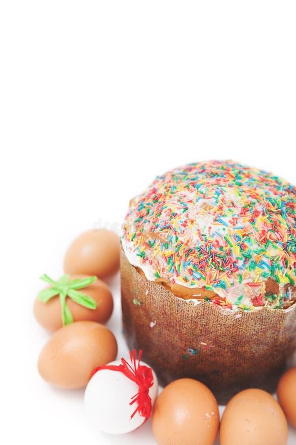 Les oeufs de pâques se trouvent autour du gâteau sur le fond blanc image libre de droits
