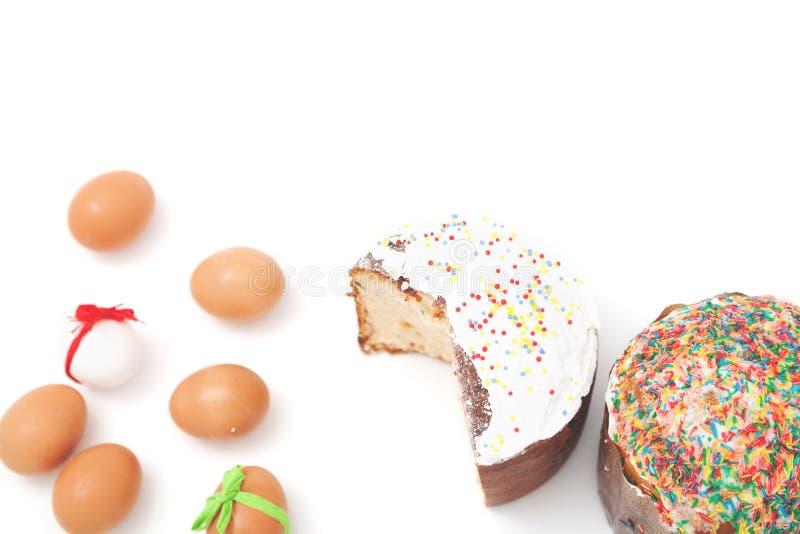 Les oeufs de pâques se trouvent autour du gâteau sur le fond blanc photos libres de droits