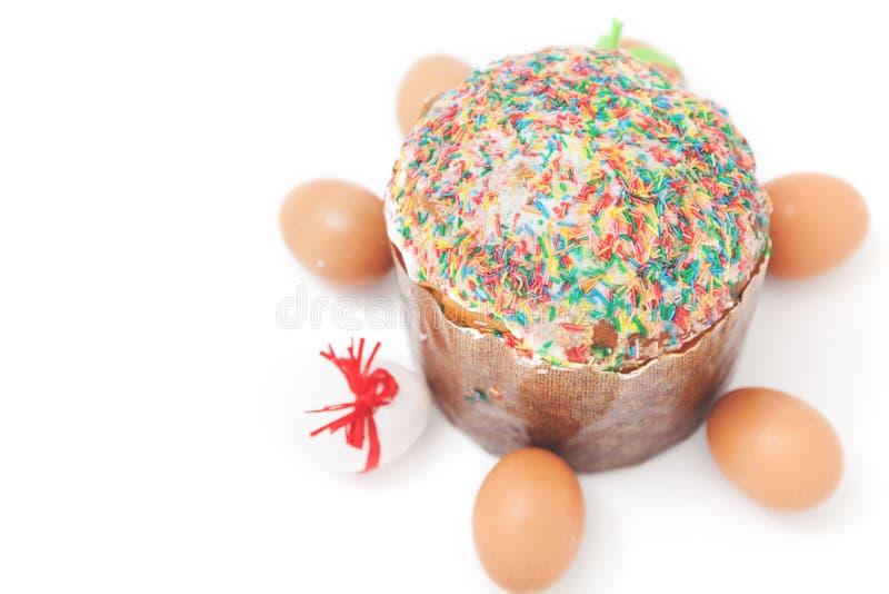 Les oeufs de pâques se trouvent autour du gâteau sur le fond blanc image stock