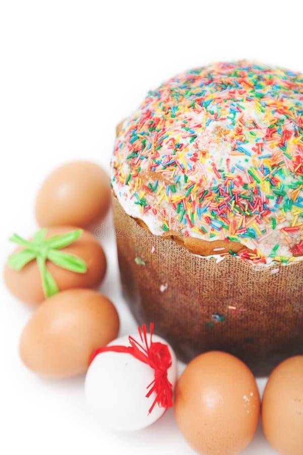 Les oeufs de pâques se trouvent autour du gâteau sur le fond blanc images libres de droits