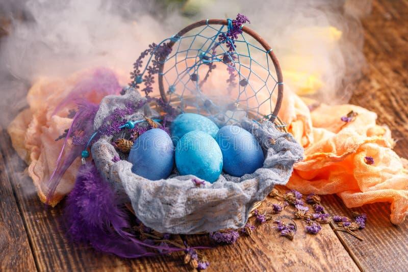 Les oeufs de pâques sont bleus avec l'attribut des rêves d'attrapeur dans la fumée image stock