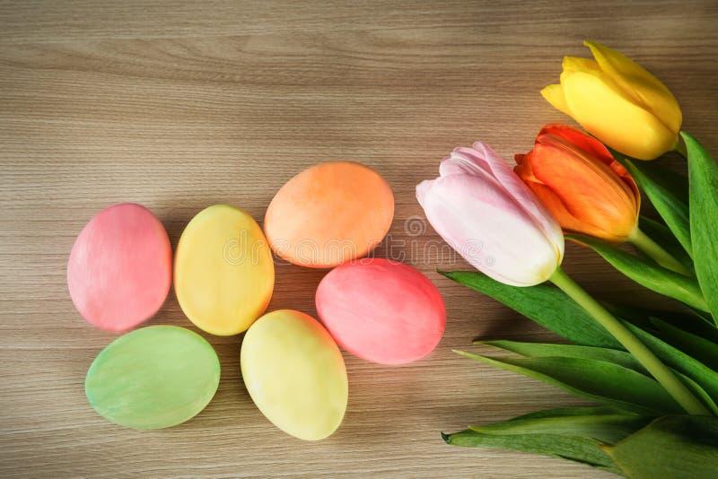 Les oeufs et le ressort peints ont coloré des tulipes sur une surface en bois image libre de droits