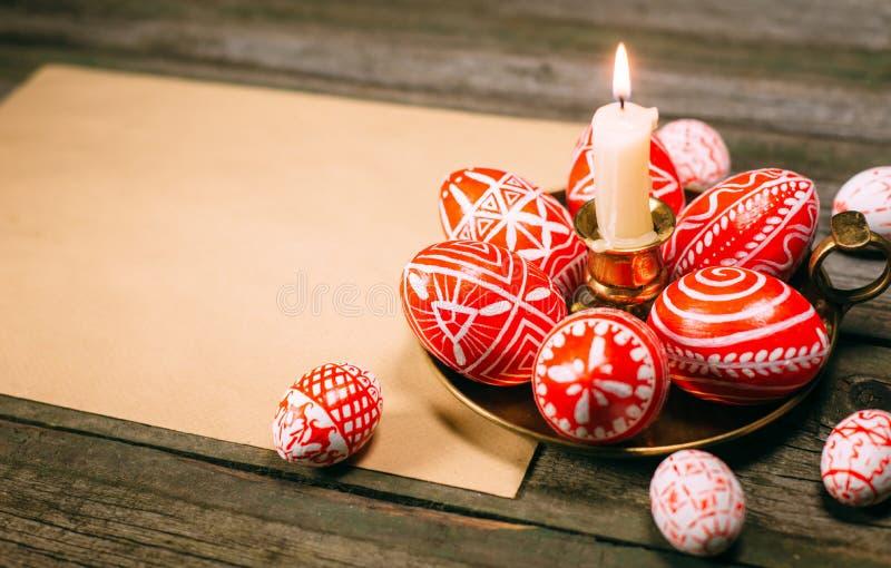 Les oeufs rouges de Pâques de plan rapproché avec le modèle blanc folklorique s'étendent autour sur le chandelier en laiton du cô images stock