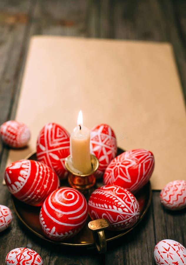 Les oeufs rouges de Pâques de plan rapproché avec le modèle blanc folklorique s'étendent autour sur le chandelier en laiton du cô photo libre de droits
