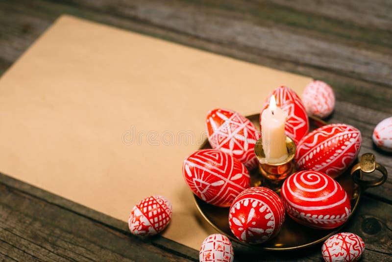 Les oeufs rouges de Pâques de plan rapproché avec le modèle blanc folklorique s'étendent autour sur le chandelier en laiton du cô photographie stock libre de droits