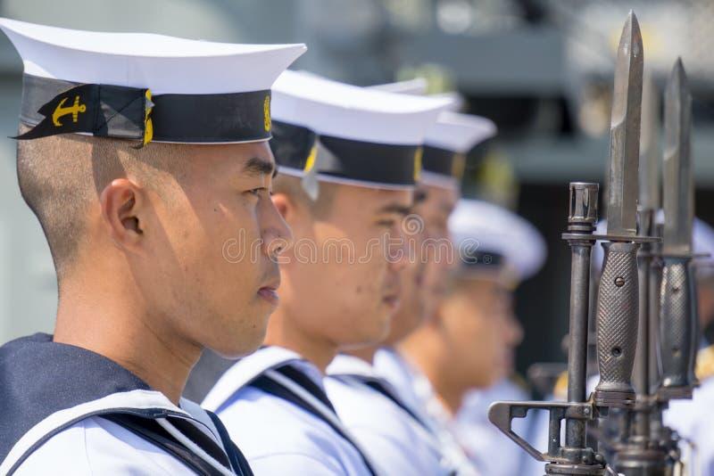 Les officiers mariniers de marine thaïlandaise royale dans la prise uniforme blanche M16 d'été fusille avec des baïonnettes photos libres de droits