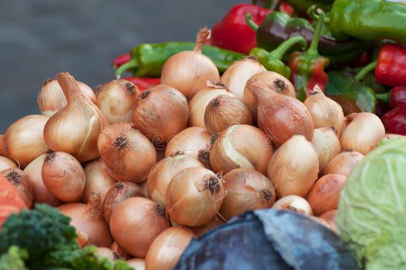 Les oignons empilent au marché photos stock