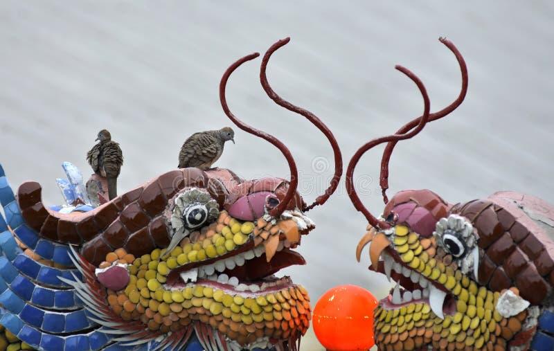 Les oiseaux étaient perché sur un dragon dans un temple chinois image libre de droits